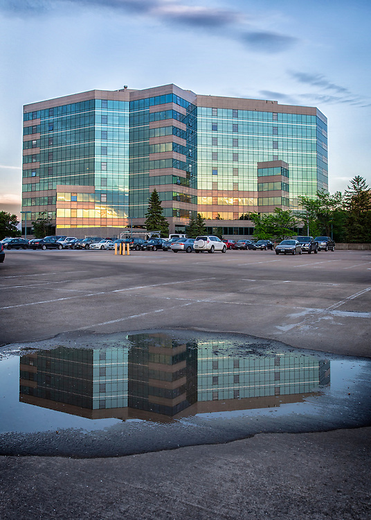 A condominium reflection in a puddle on the pavement after a rain storm