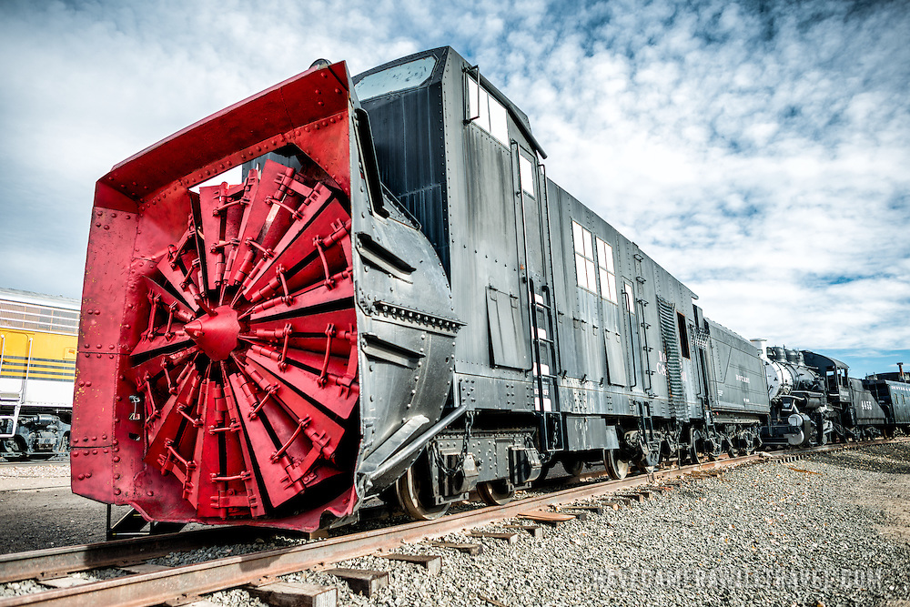 A rotary snow plow on display at the Colorado Railroad Museum in Golden, Colorado. These machines had a steam boiler and cylinders to turn the blades in front and a tender on the rear to carry the coal and water needed to fuel the boiler. The rotary plow was not self-propelled by required locomotives to push it. The big blades on the front chopped at snow and the chute directed to either side away from the tracks.