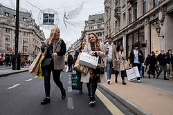 © Licensed to London News Pictures. 12/12/2020. LONDON, UK.  Shoppers in Regent Street carrying shopping bags as the number of coronavirus cases rises in the capital.  Retailers are hoping that physical sales will pick up in the run up to Christmas.  This comes against a backdrop of two major retailers Debenhams and Arcadia, owner of Topshop, collapsing into administration in recent weeks.  Photo credit: Stephen Chung/LNP
