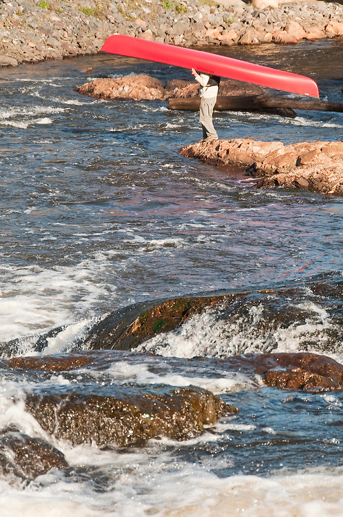A canoeist portages around a waterfall on the Dead River near Marquette Michigan.