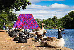 Artist Christo's 20m high installation on The Serpentine made from over 7000 barrels, titled The Mastaba, which will be on the Serpentine until 23 September 2018. The Installation is comprised of 7,506 horizontally stacked barrels. It is 20m high, 30m wide and 40m long. Hyde Park, London, June 18 2018.