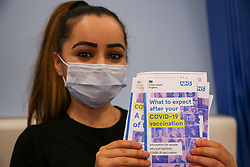 © Licensed to London News Pictures. 27/04/2021. London, UK. A woman holds NHS's 'What to expect after your COVID-19 vaccination' leaflet before receiving <br /> her Oxford/AstraZeneca vaccine at a vaccination centre in Haringey, north London. In the UK, over 33.7 million people have received a first dose and almost 12.9 million are fully vaccinated. People aged 42and over or those who will turn42before July 1, can now book their appointments through the national booking website as part of the next phase of the government's vaccination programme. <br /> <br /> ***Permission Granted*** <br />   <br /> Photo credit: Dinendra Haria/LNP