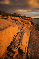 Warm glowing light at sunrise along the rocky coast of Maine, Acadia National Park, Maine, USA