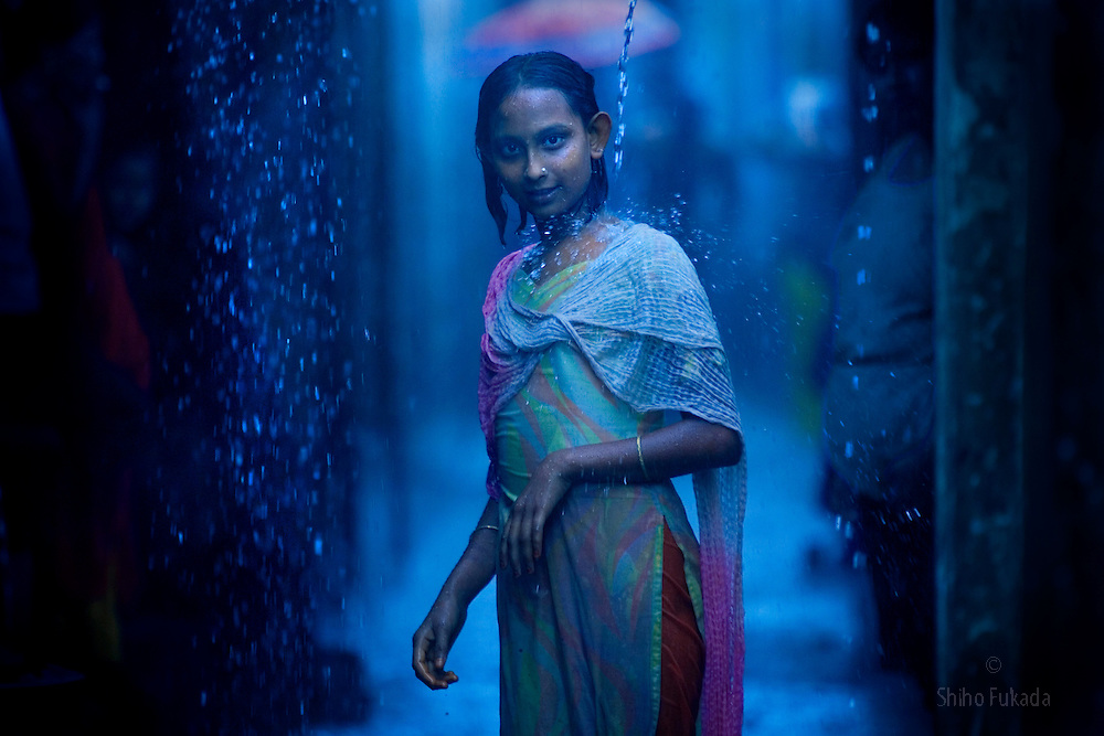 Sex worker Shumita, 12, takes rain shower at brothel in Tangail, Bangladesh. She was born into  brothel. <br /> Children who are born into brothel have limited opportunity  due to a lack of education, social prejudice, and economic difficulty. Some girls have few options but to follow her mother's footstep as a sex worker, passing the profession on to the next generation.