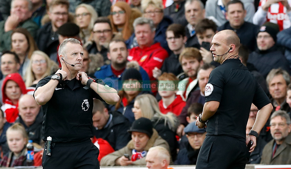 Match referee Bobby Madley (right) leaves the game and  colleague Jon Moss (left) takes over as referee