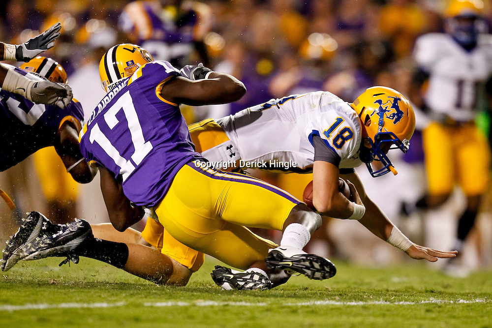 October 16, 2010; Baton Rouge, LA, USA; McNeese State Cowboys quarterback Cody Stroud (18) is tackled by LSU Tigers cornerback Morris Claiborne (17) during the first half at Tiger Stadium.  Mandatory Credit: Derick E. Hingle