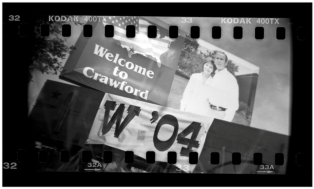 A welcome sign is seen on the road leading to Crawford, Texas, December 13, 2008. U.S. President George W. Bush moved to the small Texas town, population 705, in 1999 during his run for the presidency in 2000. The effect of the image was achieved by shooting 35mm black and white film in a medium format camera thereby exposing the entire negative including the sprocket holes of the film. REUTERS/Jim Young