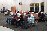 """People with face masks sit between physical and social distancing marker signs with the words """"Stay Safe. Leave Space""""  on seats in Terminal B of the San Antonio International Airport amid the global coronavirus COVID-19 pandemic, Tuesday, March 31, 2021, in San Antonio."""
