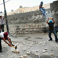 Masked Palestinian youths throw stones at Israeli security forces during clashes in the east Jerusalem neighborhood of Ras al-Amud, after Friday prayer