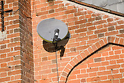 Sky television satellite dish on red brick wall of a house, UK