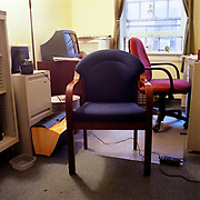 A plain wooden office chair with blue fabric in a very institutional looking office, with yellow walls and a dingy window in the background. There is an empty plastic square Tupperware dish in the left foreground, next to an open file holder, and a video camera sitting above them on a greyish file cabinet. Behind the chair is a TV in the left corner and a red office deck chair facing a metal desk on the right.