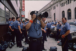 NYPD officer takes aim with a photographer's camera during the Madison Square Gardens Democratic Convention in New York, 16/07/1992