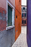 """Purple and orange alley. Burano, known for knitted lacework, fishing, and colorfully painted houses, is a small archipelago of four islands linked by bridges in the Venetian Lagoon, northern Italy, Europe. Burano's traditional house colors are strictly regulated by government. The Romans may have been first to settle Burano. Romantic Venice, the """"City of Canals,"""" stretches across 117 small islands in the marshy Venetian Lagoon along the Adriatic Sea in northeast Italy, Europe. Venice and the Venetian Lagoon are honored on UNESCO's World Heritage List."""