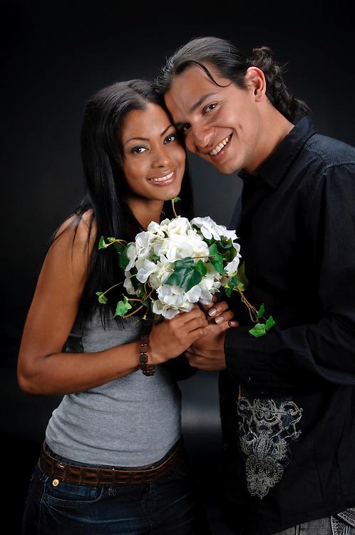 Young couple of hispanics people with black background.