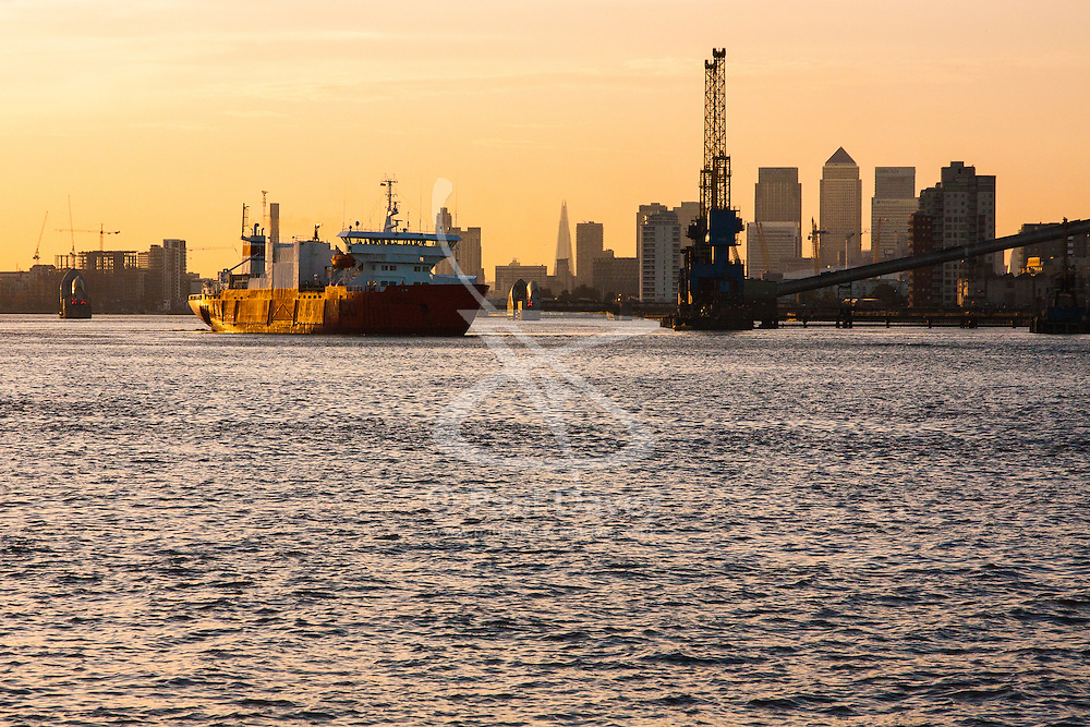 North Woolwich, London, October 28th 2014. A ship leaves the Tate and Lyle sugar factory as the late afternoon sun silhouettes Docklands.
