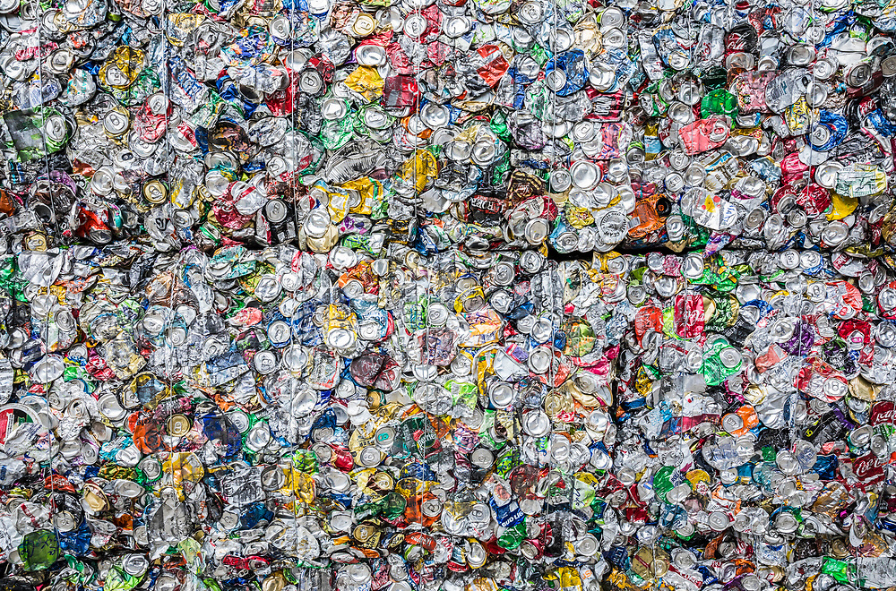 Stacked cubes or bales of aluminum cans crushed into blocks for recycling.