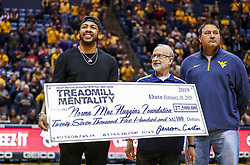 Feb 18, 2019; Morgantown, WV, USA; Memphis Grizzlies guard Jevon Carter presents a check to the Norma Mae Huggins Foundation during the first half against the Kansas State Wildcats at WVU Coliseum. Mandatory Credit: Ben Queen-USA TODAY Sports