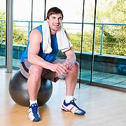 Man sitting in fitness studio on gym ball
