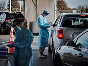 30252251A NYTVIRUS NASHVILLE, Tenn. - Dec. 30, 2020 - Sgt. Mathias Montoya with the Army National Guard, works with COVID-19 patients in the parking lot at Nissan Stadium in downtown Nashville where Meharry Medical College is conducting COVID-19 testing. Meharry is documenting around 1,000 patients a day at this location.