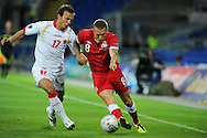 Craig Bellamy of Wales holds off Elsad Zverotic.  Euro 2012 Qualifying match, Wales v Montenegro at the Cardiff City Stadium in Cardiff  on Friday 2nd Sept 2011. Pic By  Andrew Orchard, Andrew Orchard sports photography,