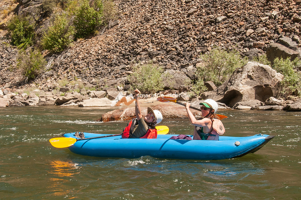 Sisters laughing while kayaking together in The Impassible Canyon on the Middle Fork of the Salmon River during six day rafting vacation, Idaho.