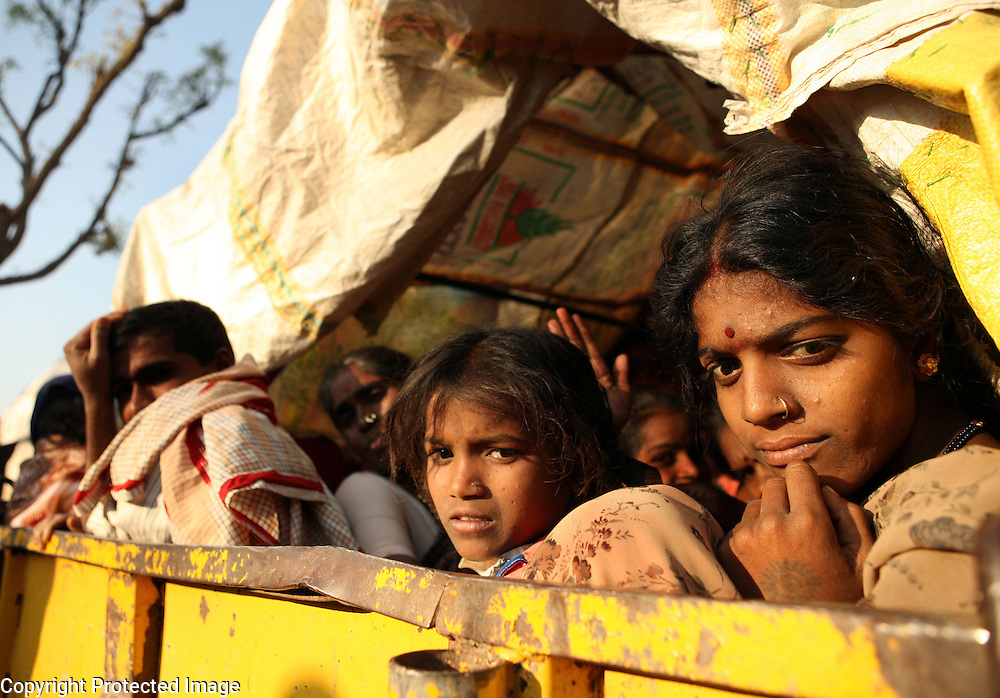 """Young girls arrrive with their family members in a bullock cart at the Yellamma Jatre (fesival) in Saundatti, India. As part of Yellamma custom, during the full moon festival which happens once a year, young girls from impoverished lower caste families are """"married"""" to the goddess Yellamma to appease her. Once they are married to Yellamma, they are regarded as servants to the goddess and must perfrom temple duties as well as satisfy the sexual needs of the priests and other men.  They may no longer marry a mortal and often end up being sold by unscrupulous priests to pimps who take them to work in the red-light districts of India's urban areas. Girls with matted hair, bad skin or disabilities like blindness are most likely to be chosen as Devadasis as these qualitites are considered Yellamma's calling card."""