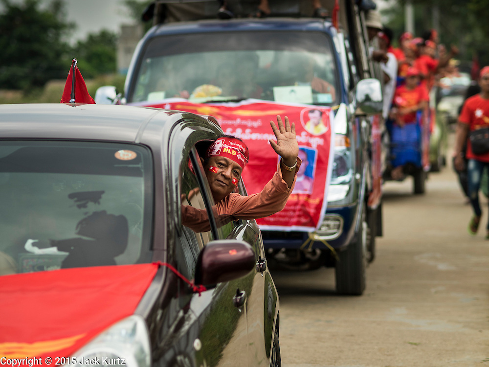 25 OCTOBER 2015 - SHWEPYITHAR, MYANMAR: A National League for Democracy (NLD) supporter waves during a party motorcade in Shwepyithar, Myanmar. Political parties are in fill campaign mode in Myanmar (Burma). National elections are scheduled for Sunday Nov. 8. The two principal parties are the National League for Democracy (NLD), the party of democracy icon and Nobel Peace Prize winner Aung San Suu Kyi, and the ruling Union Solidarity and Development Party (USDP), led by incumbent President Thein Sein. There are more than 30 parties campaigning for national and local offices.     PHOTO BY JACK KURTZ