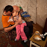 Vitaly cares for his fifteen year old daughter Sasha in their one bedroom appartment in the city of Gomel in Southern Belarus.He cares for her during the day and must go to work as a night watchman each evening.<br /> Chernobyl's human costs are widespread affecting about seven million people.A generation later children are being born with birth defects ,heart problems and thyroid cancer.The crippled economy of Belarus has led to poverty, social problems and domestic abuse.<br /> Photograph by Eamon Ward