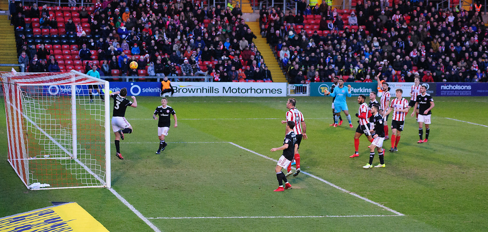 Accrington Stanley's Mark Hughes heads an effort from Lincoln City's Harry Anderson (top right) over the cross bar<br /> <br /> Photographer Chris Vaughan/CameraSport<br /> <br /> The EFL Sky Bet League Two - Lincoln City v Accrington Stanley - Saturday 16th December 2017 - Sincil Bank - Lincoln<br /> <br /> World Copyright © 2017 CameraSport. All rights reserved. 43 Linden Ave. Countesthorpe. Leicester. England. LE8 5PG - Tel: +44 (0) 116 277 4147 - admin@camerasport.com - www.camerasport.com