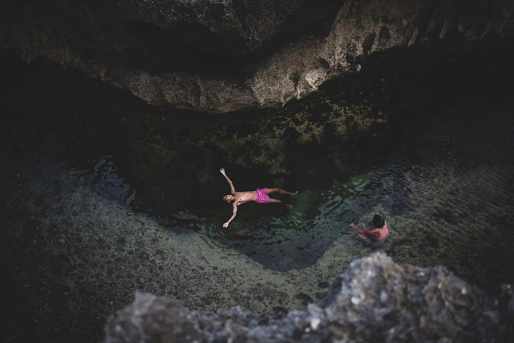 Nusa Penida, Bali, Indonesia - October 3, 2017: A man floats on his back, arms outstretched, at Angel's Billabong on the island of Nusa Penida.