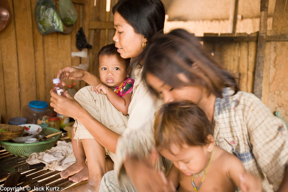30 JUNE 2006 - PHNOM PENH, CAMBODIA: The wife and children of a brick factory worker in their hut at a brick factory in Phnom Penh, Cambodia. This particular factory employs about 30 people. The live on the premises with their families. Most of the workers migrated to Phnom Penh from the countryside looking for better paying jobs than they could find in the countryside. According the United Nations Food and Agricultural Organization, there are more than 70 brick factories in Phnom Penh and its environs. Environmentalists are concerned that the factories, most of which burn wood in their kilns, contribute to deforestation in Cambodia. They are encouraging factory owners to switch to burning rice husks, as brick kilns in neighboring Vietnam do. The brick factories are kept busy feeding Phnom Penh's nearly insatiable appetite for building materials as the city is in the midst of a building boom brought by on economic development and the need for new office complexes and tourist hotels.   Photo by Jack Kurtz / ZUMA Press