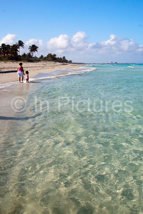 Mother and daughter two 2 people walking along Varadero beach in Matanzas province, Cuba's most popular beach resort welcoming thousands of guests every year from all over the world.
