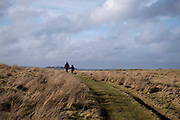 A woman holds hand with her child as they walk along a foot path on the working hill farm at Carreg Cennen on 18th February 2019 in Trapp, Powys, Wales, United Kingdom.