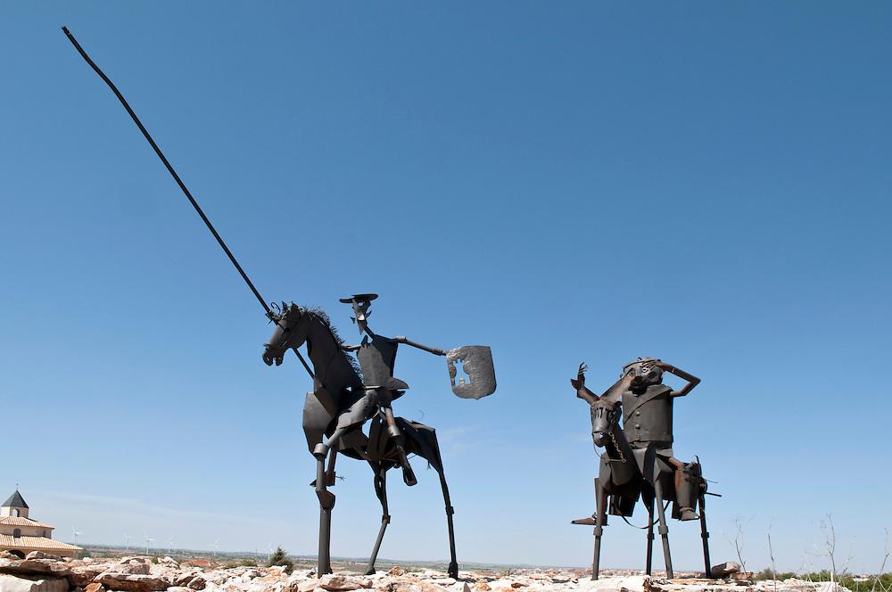 Eine Eisenskulptur der Romanfiguren Don Quijote - Don Quichotte -  (l.) und Sancho Pansa de la Mancha, nach dem ersten Roman der Neuzeit des Schriftstellers Miguel de Cervantes, steht in der spanischen Landschaft  La Manchas nahe des Ortes Munera in der Sierra de Alcaraz Campo do Moniel. Im Hintergrund Windräder |  sculpture of Don Quichotte de La Mancha close to the village of Murena