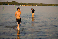 boy in lake running toward shore while swimming in Minnesota lake with friends