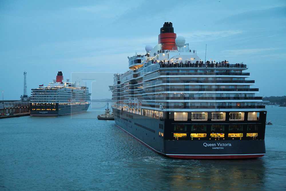 © Licensed to London News Pictures. 09/05/2014. Southampton, UK. Queen Victoria (right) moves into position herself on the stern of Queen Elizabeth (left) at the Queen Elizabeth 2 berth in Southampton. Firework celebrations marking the 10-year anniversary of the Cunard flagship, Queen Mary 2, take place in the port of Southampton this evening, 9th May 2014. All 'three queens' of the Cunard fleet were present at the event, which included a 10-minute firework display, one minute for every year that the QM2 has been in service. Photo credit : Rob Arnold/LNP