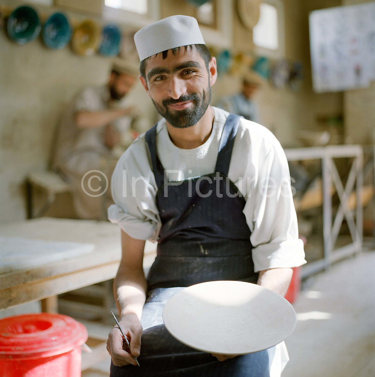 Jawid, a third year Ceramics student from Istalif, working on a kick-wheel in the Ceramics School.  Jawid is one of fifteen trainee potters working at Turquoise Mountain to improve his skills in glaze and clay techniques.  This new knowledge will help Jawid to attract new business and make high quality pots when he graduates from the three-year programme. The Turquoise Mountain Foundation is a non-profit, non-governmental organization which invests in Afghanistan's traditional crafts, historic building and landscapes in order to preserve cultural heritage, improve living conditions and create economic opportunities.