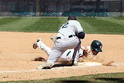 14 April 2013:  Anthony Lopez dives for the first base bag as Luke Collins fields the pick off throw from the pitcher during an NCAA division 3 College Conference of Illinois and Wisconsin (CCIW) Baseball game between the Elmhurst Bluejays and the Illinois Wesleyan Titans in Jack Horenberger Stadium, Bloomington IL