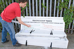 Teenaged boy recycling fluorescent light tubes at city tip,