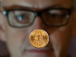 © Licensed to London News Pictures. 02/03/2012. London, UK. Peter Swanston CEO of the London Mint looking at a rare American 1933 Double Eagle coin on display at Goldsmiths Hall in London for the first time. In 2002, a 1933 Double Eagle sold for 7.6 million dollars, making it the most expensive gold coin in the world to come to auction up to that time. Photo credit : Ben Cawthra/LNP