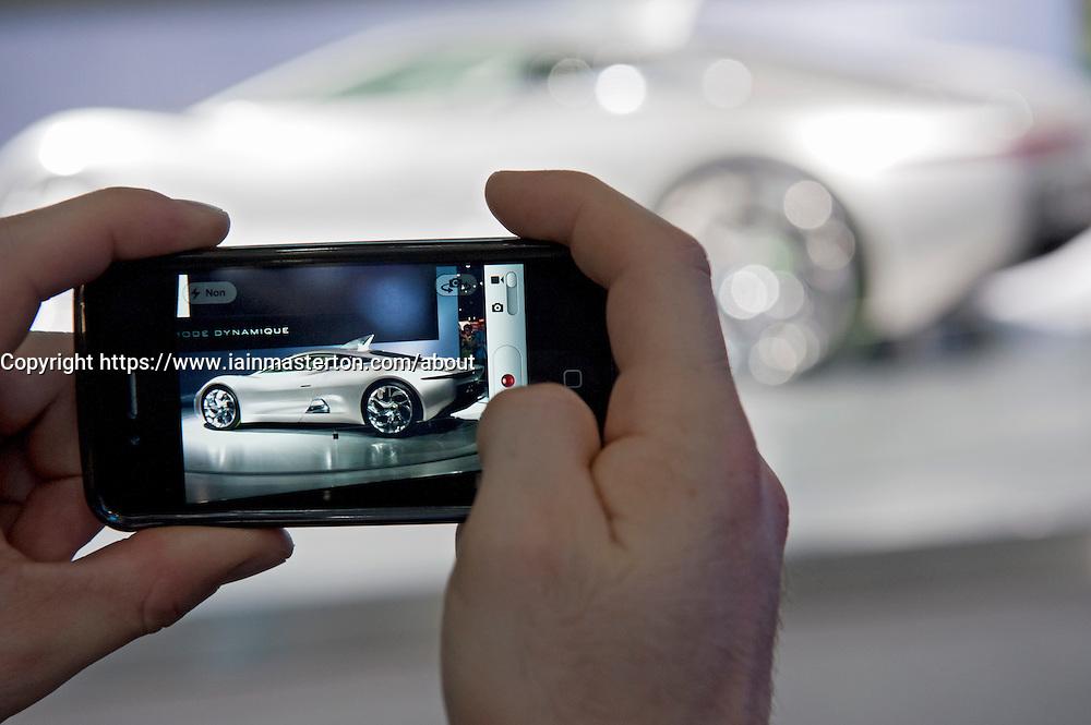 New Jaguar sports car viewed through camera phone at the Paris Motor Show 2010