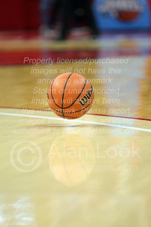 a basketball bounces on a gym floor