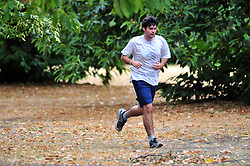 © Licensed to London News Pictures. 30/07/2018<br /> GREENWICH, UK.<br /> A man jogging with brown leaves on the ground.<br /> A cloudy grey day in London, Greenwich Park, Greenwich.<br /> Photo credit: Grant Falvey/LNP