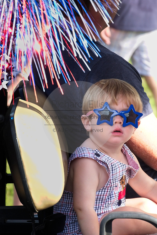 A young child wears stars and stripes sunglasses during the annual Sullivan's Island Independence Day parade July 4, 2017 in Sullivan's Island, South Carolina. The tiny affluent sea island hosts a bicycle and golf cart parade through the historic village.