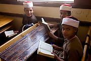 A portrait of schoolboys holding their copies of the Koran in a classroom at the Islamic Koom al-Bourit Institute for Boys in the village of Qum (Koom), on the West Bank of Luxor, Nile Valley, Egypt.