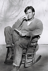Man sitting in a wooden rocking chair with a book in his hand