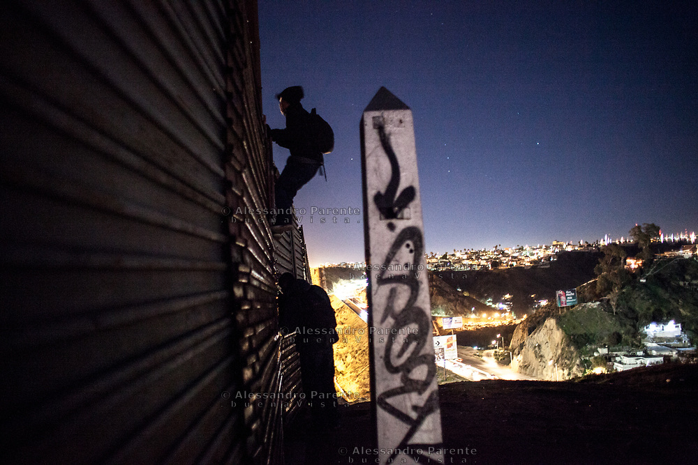 Migrant from Honduras watching from the top of the border.