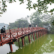 The Huc Bridge with tourists. The red-painted, wooden bridge joins the northern shore of the lake with Jade Island and the Temple of the Jade Mountain (Ngoc Son Temple).