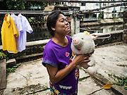 30 JULY 2016 - BANGKOK, THAILAND:  A woman brings in her daughter's plush toy after she washed it in community laundry drying area in the Pom Mahakan Fort slum. The community is known for fireworks, fighting cocks and bird cages. Mahakan Fort was built in 1783 during the reign of Siamese King Rama I. It was one of 14 fortresses designed to protect Bangkok from foreign invaders. Only of two are remaining, the others have been torn down. A community developed in the fort when people started building houses and moving into it during the reign of King Rama V (1868-1910). The land was expropriated by Bangkok city government in 1992, but the people living in the fort refused to move. In 2004 courts ruled against the residents and said the city could take the land. Eviction notices have been posted in the community and people given until April 30 to leave, but most residents have refused to move. Residents think Bangkok city officials will start evictions around August 15, but there has not been any official word from the city.     PHOTO BY JACK KURTZ