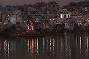 Sarovar or Pushkar Lake with it's 52 Ghats to bath. Pushkar, Rajasthan. INDIA<br /> The devout who have come from all races who have mingled in Rajasthan come here dressed in their finest clothes and jewellery to bath in the lake. The most prominant colour saris and turbins seen during the pilgrimage are yellow, orange and red and white. Rajasthani men are famous for their elaborate and often very large turbins and moustaches.<br /> The town of Pushkar is one of the holiest centers of Hinduism and houses one of the few Brahma Temples in India. It is one of the 5 essential pilgrimage centers which a Hindu must visit in his lifetime along with Badrinath, Puri, Rameshwaram and Dwarka. The 12 day camel and livestock fair culminates in a religious Hindu pilgrimage and reaches a crescendo on the night of the full moon (Purnima) when pilgrims take a dip in the holy lake.  <br /> Pushkar camel and livestock fair takes place in the Hindu month of Kartik (October / November) ten days after Diwali (Festival of Lights). Pushkar has always been the the region's main market for herdsman and farmers buying and selling camels, horses, indigenous breeds of cattle and even elephants. Over the years this annual trading event has increased in volume to become one of the largest in Asia. Temporary tents and campsites suddenly appear to accomodate the thousands of pilgrims, villagers and tourists. Entertainers and contests abound and a festive funfair atmosphere prevails over Pushkar during the Mela's 2 week duration. Thousands of men come first with their camels, horses and cattle and camp on the dunes to transact business. 3 days before the full moon the women arrive beautifully attired for the pilgrimage.